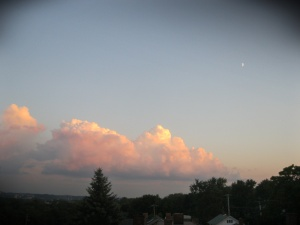 Summer cloud and moon at sunset
