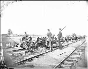Soldiers guarding damaged O&A rail road rolling stock, August 1862.