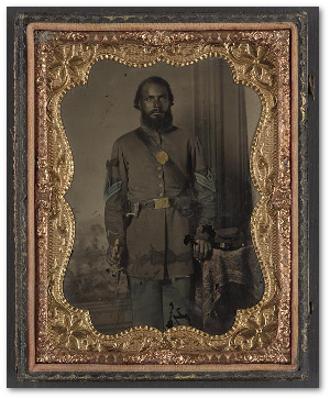 Unidentified African American soldier in Union infantry sergeant's uniform and black mourning ribbon with bayonet in front of painted backdrop, between 1863 and 1865.  (Library of Congress)
