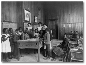 African American children learning about Thanksgiving, with model log cabin on table, Whittier Primary School, Hampton, Virginia, in 1899 or 1900.  (Library of Congress)