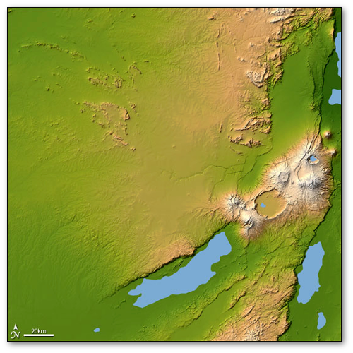 Ngorongoro is a wildlife refuge and UNESCO World Heritage Site.  That faint horizontal line in the middle of the picture is Olduvai Gorge.  The Serengeti Plain is in the upper left.  (NASA)