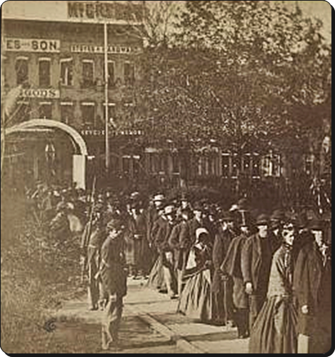"Per the Library of Congress, ""[A] group of citizens entering the grounds of the Illinois state house to view the body of Abraham Lincoln on May 3 or 4, 1865. Two soldiers stand near the specially built arch. The African American man with the cane near the head of the line is Reverend Henry Brown."""