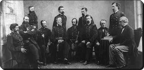 Left to right, standing: Generals Thomas Harris, Lew Wallace,  and August Kautz; Mr. Henry Burnett. Seated left to right: Colonels David Clendenin and C.H. Tompkins; Generals Albion Howe, James Ekin, David Hunter,and Robert S. Foster'; Mr. John A. Binham; and General Joseph Holt.